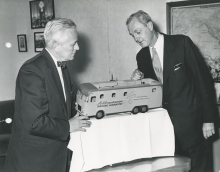 The Head of the US delegation to the IAEA, Robert McKinney (right) describing the equipment inside a model of one of the mobile labs to the Director General of the IAEA, William Sterling Cole (left). 29 April 1958. Please credit IAEA