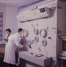 Hans Grasmuk and Olga Milosevic-Golwig, staff members, in front of the hot cell used for the remote handling of radioisotopes at the IAEA laboratory in Seibersdorf. April 1964. Please credit IAEA