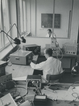 Foreground - counters and generators from seven nations: Japan, UK, France, USA, Poland, Federal Republic of Germany and the Netherlands. Through the window - Dr. Keroe in his office.  October 1961. Please credit IAEA