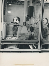 Installation presented by the French Government.  The picture shows the interior of the airtight cell, the lead-shielding and, through the radiation proof window, Professor Alexandre Sanielevici, of the Division of Research and Laboratories, opening a container with the help of a manipulator (left foreground).  February 1963.  Please credit IAEA