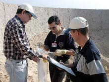 IAEA inspectors take a smear sample from a test range. Photo Credits: Pavlicek/IAEA