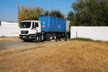 Truck with ISO transport container containing the IIN-3M Foton rector's irradiated liquid HEU fuel is leaving the site of the Radiation and Technological Complex in Tashkent, Uzbekistan. After draining the HEU fuel from the reactor core, it was safely and securely placed into transport canisters, which were then loaded carefully onto a SKODA VPVR/M spent fuel shipment container. That container is inside the standard, blue transport container on the truck. (Photo: S. Tozser/IAEA)