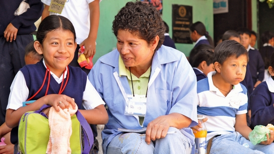 A field worker discusses the benefits of good nutrition at an urban primary school in Guatemala