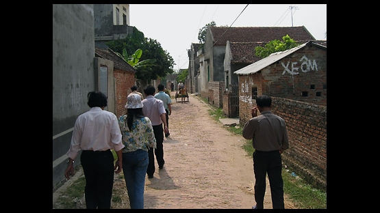 Photo 1 of 15 : The village streets of Thanh Gia in north Vietnam's rice-rich Red River region.  Families in this small hamlet of Bac Ninh Province have been living off the land and rice farming for centuries.  As a mule-drawn cart approaches, a painted sign promoting 'Xe Om' -- or motorbike taxi -- suggests a more modern road ahead.